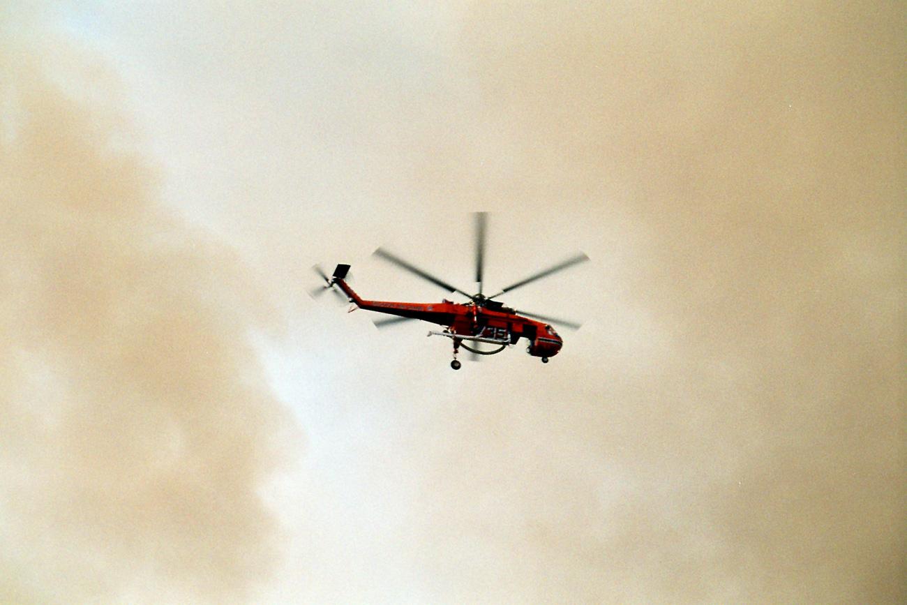 Ein Helikopter beteiligt sich an den Löscharbeiten, von dichtem Qualm umhüllt. Gesehen zwischen Githion und Monemvassia auf dem Peloponnes.